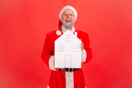 Positive smiling man in santa claus costume holding paper house in hands looking at camera with excited expression, dreams comes true on holidays. Indoor studio shot isolated on red background
