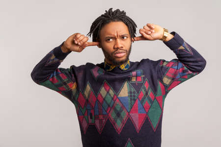 I dont want to hear this. Annoyed frustrated african guy with dreadlocks closing ears with fingers ignoring information, tired of irritating noise. Indoor studio shot isolated on gray background