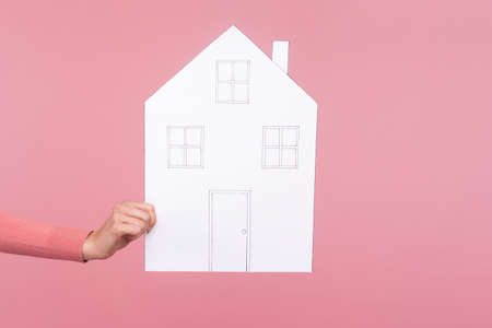Closeup side view female holding white paper model of house, dreams about own accommodation, real estate agency. Indoor studio shot isolated on pink background