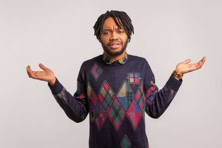 I dont know. Confused african man with beard and dreadlocks throwing up his hands, puzzled, uncertain, cant find answer to question. Indoor studio shot isolated on gray background