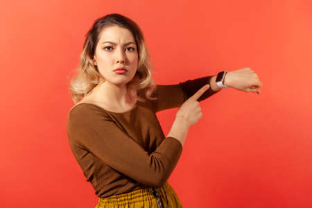 We have no time! Portrait of serious boss woman with blonde hair in brown blouse pointing her finger at the smartwatch and getting angry. Indoor studio shot isolated on red background