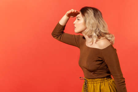 Side view portrait of curious blonde woman holding hand above eyes and peering into distance, looking far away, expecting and searching someone. Indoor studio shot isolated on red background Foto de archivo