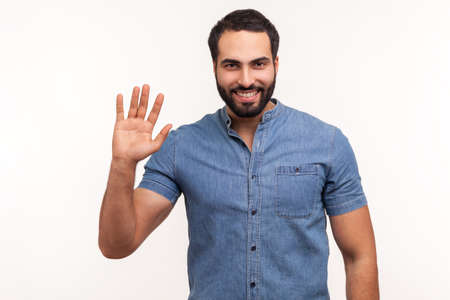 Friendly positive bearded man in blue shirt greeting you rising hand and waving, saying hi, glad to see you, looking at camera with toothy smile. Indoor studio shot isolated on white background Standard-Bild