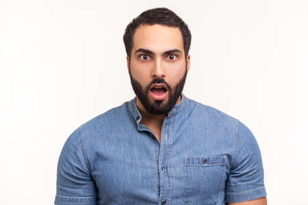 Surprised wondered man with beard in blue shirt looking at camera with big eyes and open mouth, shocked with unexpected news. Indoor studio shot isolated on white background