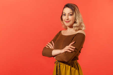 Portrait of happy attractive confident young woman with blonde hair in brown blouse standing with crossed arms and looking at camera with smile. Indoor studio shot isolated on red background