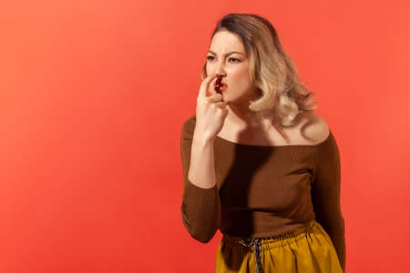This is lie! Portrait of angry woman with blonde hair touching nose, showing liar gesture, expressing distrust of false suggestion, deception. Indoor studio shot isolated on red background