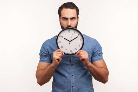 Bossy serious man with beard holding in hands big wall clock looking at camera with displeased, time to act, countdown. Indoor studio shot isolated on white background