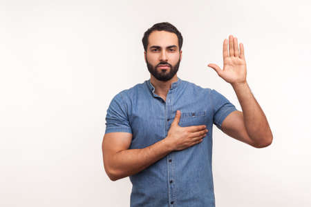I swear! Conscious honest man raising one hand and holding on chest another, swearing in honesty and devotion, patriotism. Indoor studio shot isolated on white background Banco de Imagens