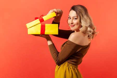 Side view beautiful woman unpacking big yellow gift box and looking at camera with pleasant smile, satisfied with present. Indoor studio shot isolated on orange background Banque d'images