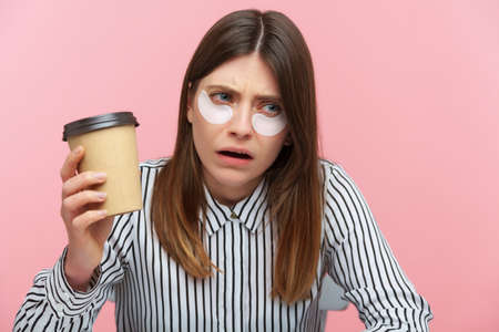 Exhausted tired woman with brown hair in striped shirt drinking coffee from paper cup sitting with patches under eyes, looking for energy and motivation. Indoor studio shot isolated on pink background
