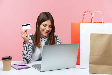 Happy excited woman sitting at laptop and holding credit card, doing shopping online, paper bags lying on desk, fast delivery service. Indoor studio shot isolated on pink background