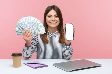 Positive happy woman office worker holding dollar bills and empty screen smartphone sitting at workplace, laptop, notepad and paper cup lying on desk. Indoor studio shot isolated on pink background Фото со стока