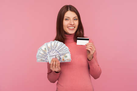 Happy satisfied woman with brown hair in pink sweater holding credit card and fan of dollar cash looking at camera with toothy smile. Indoor studio shot isolated on pink background Banque d'images