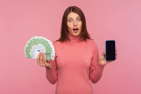 Extremely surprised brunette woman in pink sweater holding smartphone with empty screen and fan of euros looking at camera with shocked expression. Indoor studio shot isolated on pink background Banque d'images