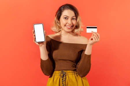 Smiling positive woman holding and showing white screen smartphone and credit card, easy banking, online crediting. Indoor studio shot isolated on orange background