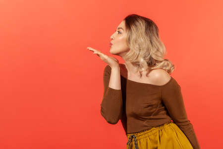 Romantic feelings, devotion. Side view of beautiful woman in brown blouse sending sensual air kiss to side, looking with love and affection, flirting. Indoor studio shot isolated on red background