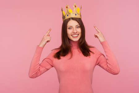 Happy cheerful brunette woman in pink sweater pointing fingers on golden crown on her head, showing her leadership qualities, concept of authority. Indoor studio shot isolated on pink background
