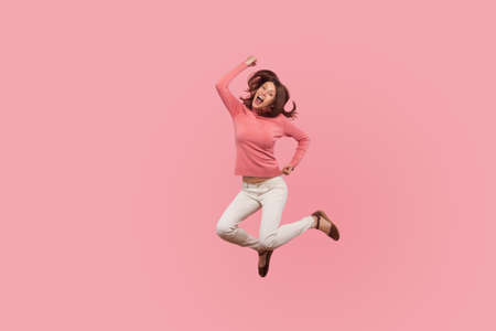 Extremely happy satisfied woman jumping high celebrating her success, flying in air with pleased smiling expression, dreams comes true. Indoor studio shot isolated on pink background