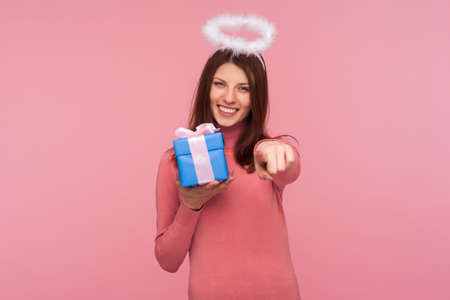 Happy birthday to you! Angelic brunette woman with nimbus over head giving present and pointing finger to camera, sharing holiday gift, congratulating. Indoor studio shot isolated on pink background