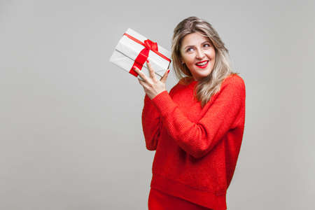 Portrait of interested beautiful blonde woman with red lipstick in casual sweater, listening to wrapped gift box, curious about birthday surprise. indoor studio shot isolated on gray background