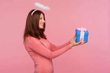 Profile portrait of brunette woman with nimbus above her head holding blue gift box in hands, making present to you, congratulation on holidays. Indoor studio shot isolated on pink background Banque d'images