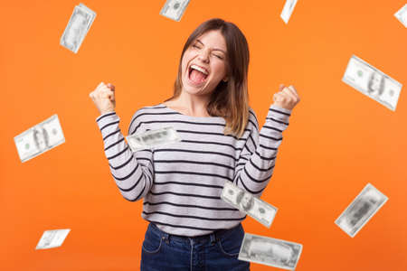 Money rain. Yes I did it! Portrait of joyous winner, young woman in casual shirt standing with clenched fists and closed eyes, celebrating victory and richness. indoor isolated on orange background
