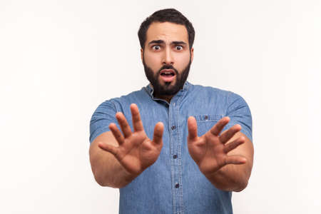 Scared confused lonely man in blue shirt stretching his hands trying to hide, afraid to go in darkness, suffering from panic attack. Indoor studio shot isolated on white background