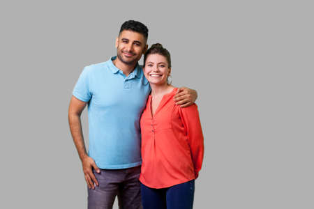 Portrait of young attractive family couple in casual wear standing together, embracing and looking at camera with sincere smile, strong relations. isolated on gray background, indoor studio shot