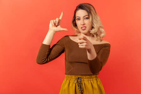 You are loser! Portrait of beautiful young woman with blond hair looking at the camera she pointing at camera and showing loser gesture. Indoor studio shot isolated on red background.