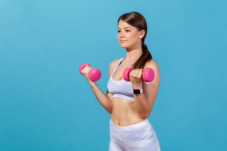 Self confident athletic woman in white sportswear doing sport exercises with pink dumbbells, pumping up muscles, power and endurance. Indoor studio shot isolated on blue background