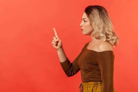 Warning sign. Side view portrait of young adult confident lady boss or teacher looking at the side with serious face and finger warning gesture. Indoor studio shot isolated on red background 版權商用圖片