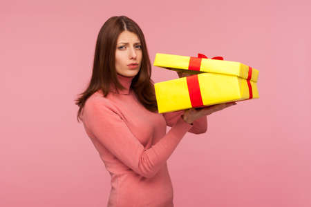 Capricious unhappy woman with brown hair in pink sweater disappointed with her birthday gift, holding unpacked present box in hands. Indoor studio shot isolated on pink background Imagens