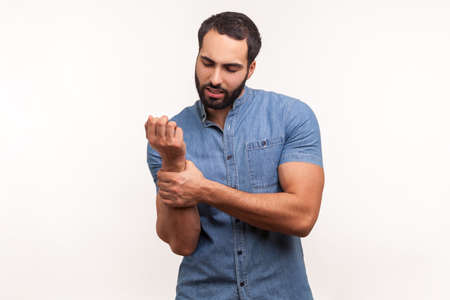 Unhappy sick bearded man in blue shirt touching painful hand, suffering trauma, sprain wrist, feeling ache of carpal tunnel syndrome. Indoor studio shot isolated on white background