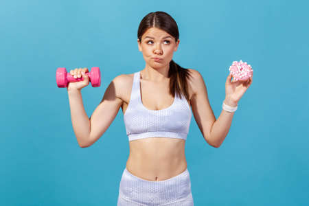 Confused athletic woman in white sportswear holding in hands pink dumbbell and donut with pink glaze, making hard choice, succumb to seduction. Indoor studio shot isolated on blue background