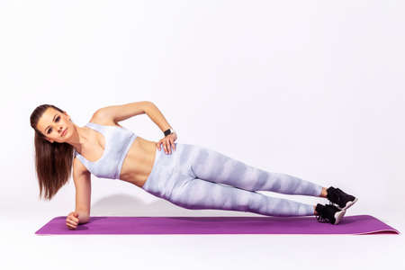 Full length fitness woman in white sportswear practicing yoga, doing Vasisthasana exercise with one hand raised, doing side plank pose, training muscles. Indoor studio shot isolated on gray background