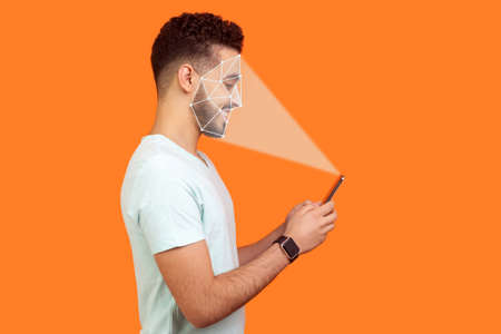 Mobile biometric identification and verification or detection concept. face ID scaning or unlocking technology. happy man using facial recognition on smartphone. indoor isolated on orange background.