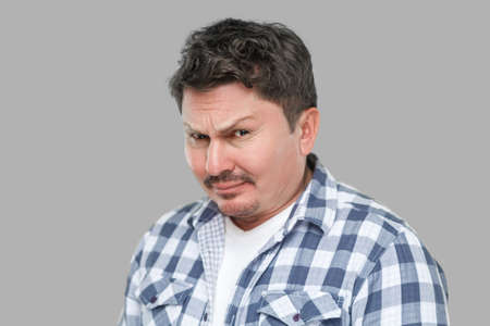 closeup portrait of serious handsome middle aged business man in casual checkered shirt standing and looking at camera with doubtful face. indoor studio shot, isolated on gray background.