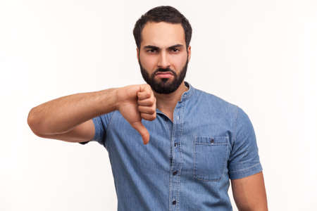 Unhappy dissatisfied man with beard showing thumbs down dislike gesture, symbol of disagree, giving feedback. Indoor studio shot isolated on white background