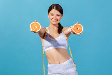Slim happy woman in sportswear with tape line on shoulders holding and showing ripe juicy grapefruit halves, losing extra centimeter keeping citrus diet. Indoor studio shot isolated on blue background