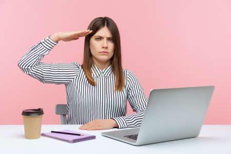 Yes sir! Obedient responsible business woman sitting at workplace with laptop and saluting, listening to boss order, corporate discipline. Indoor studio shot isolated on pink background