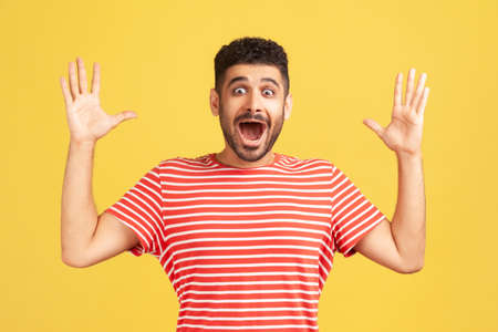 Shocked surprised bearded man in red striped t-shirt looking at camera with big eyes and widely opened mouth, amazed and excited. Indoor studio shot isolated on yellow background