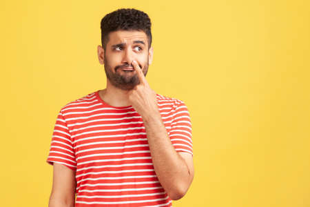 Uncultured bored bearded man in red striped t-shirt putting finger inside nose and drilling, fooling around, showing his bad manners. Indoor studio shot isolated on yellow background Foto de archivo