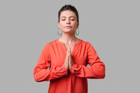 Portrait of calm beautiful girl with bun hairstyle, big earrings and in red blouse standing with closed eyes and holding arms in prayer, yoga for peace. indoor studio shot isolated on gray background Stock Photo