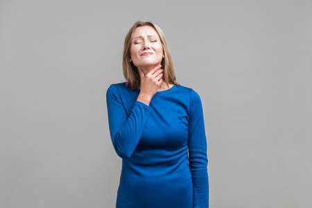 Throat pain. Portrait of unhappy ill woman in elegant tight blue dress touching her neck, suffering sore throat, viral infection or flu symptoms. indoor studio shot isolated on gray background