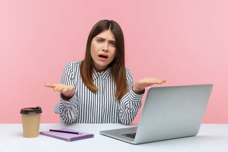 What do you want? Upset irritated woman office worker spreading hands sitting at workplace with laptop, looking at camera with angry nervous expression. Indoor studio shot isolated on pink background Imagens