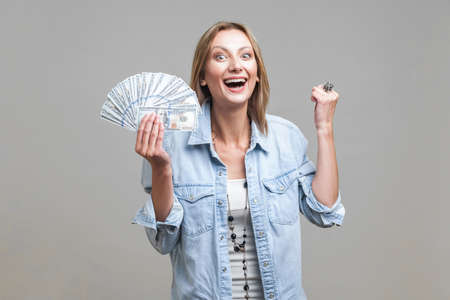 Portrait of extremely happy woman in denim shirt holding fan of dollars, smiling with teeth and showing yes i did it gesture, celebrating big income. indoor studio shot isolated on gray background