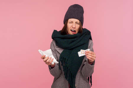 Upset depressed sick woman in hat and warm scarf holding napkin and pills, frowning with displeased miserable expression. Indoor studio shot isolated on pink background