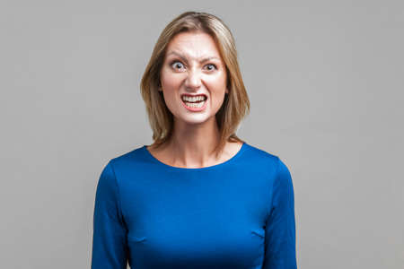 Portrait of beautiful emotional woman in tight blue dress standing with clenched teeth and angry grimace on face, pretending to be aggressive. indoor studio shot isolated on gray background Zdjęcie Seryjne