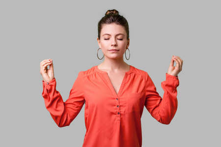 Portrait of peaceful young woman with bun hairstyle, big earrings and in red blouse relaxing and doing meditation gesture with fingers, practicing yoga. indoor studio shot isolated on gray background