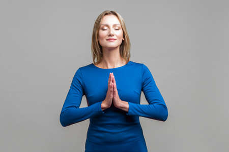 Harmony of mind. Portrait of elegant woman in blue dress standing with closed eyes and peaceful calm face meditating, holding hands in prayer. indoor studio shot isolated on gray background